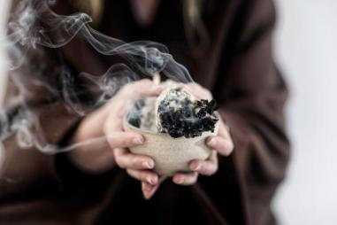 Hands_of_a_spiritual_woman_holding_burning_smoking_Sage_Smudge_stick__smudging_810_500_75_s_c1.jpg