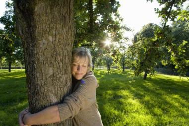 Mature_woman_embracing_tree__eyes_closed__tree_hugging__tree_huggers_810_500_75_s_c1.jpg